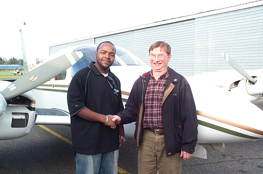 Christopher Russell receives contratulations form Pilot Examiner Captain John Laing.  Langley Flying School.